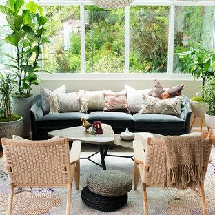 Cette photo montre une véranda éclectique avec un sol en bois brun, un plafond en verre et un sol marron.