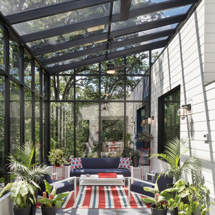 Design ideas for a large modern conservatory in Minneapolis with a glass ceiling and grey floors.