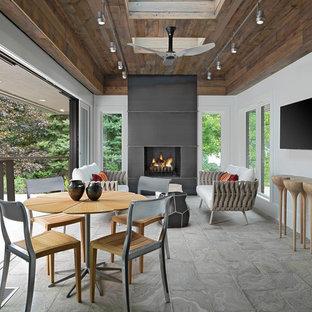 Idées déco pour une très grand véranda moderne avec un sol en travertin, une cheminée standard, un manteau de cheminée en métal, un puits de lumière et un sol gris.