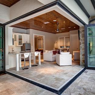 Klassisk inredning av ett stort uterum, med kalkstensgolv, tak och beiget golv