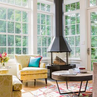 Aménagement d'une véranda classique de taille moyenne avec un sol en bois brun et cheminée suspendue.