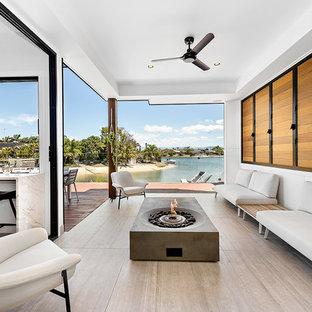 Foto på ett funkis uterum, med klinkergolv i porslin, grått golv, en spiselkrans i betong och tak