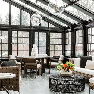 Cette image montre une grand véranda traditionnelle avec aucune cheminée, un plafond en verre, un sol en ardoise et un sol gris.