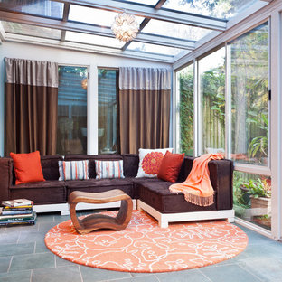 Example of an eclectic gray floor sunroom design in New York with a glass ceiling