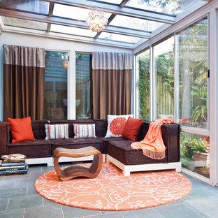 Cette image montre une véranda bohème avec un plafond en verre et un sol gris.