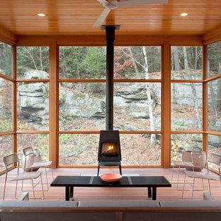 Inspiration för rustika uterum, med mellanmörkt trägolv, en öppen vedspis och tak