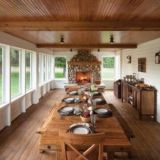 Inspiration pour une grand véranda rustique avec un sol en bois foncé, une cheminée standard, un manteau de cheminée en pierre, un plafond standard et un sol marron.