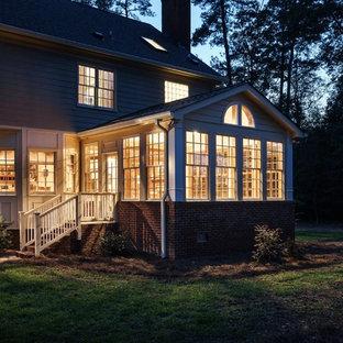 Cette photo montre une véranda chic de taille moyenne avec un sol en bois clair et un plafond standard.