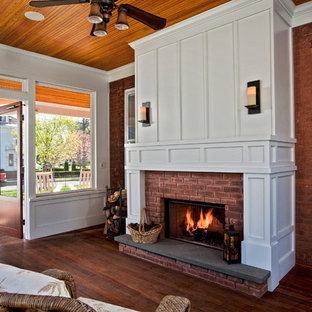 Réalisation d'une véranda tradition de taille moyenne avec un sol en bois foncé, un plafond standard, un manteau de cheminée en brique et une cheminée standard.