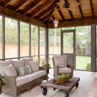 Foto på ett stort lantligt uterum, med travertin golv, en standard öppen spis och tak