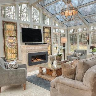 Cette photo montre une grand véranda éclectique avec un sol en marbre, aucune cheminée, un manteau de cheminée en pierre, un sol gris et un puits de lumière.