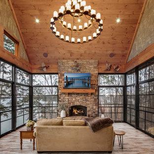 Exemple d'une véranda montagne de taille moyenne avec un sol en bois brun, une cheminée standard, un manteau de cheminée en pierre, un plafond standard et un sol marron.