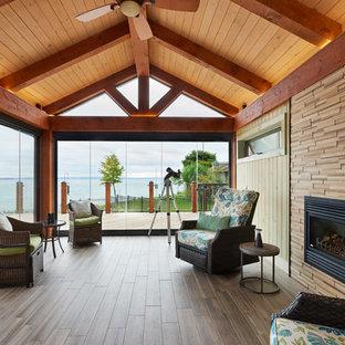 Immagine di una veranda stile americano di medie dimensioni con pavimento in gres porcellanato, camino classico e cornice del camino in legno