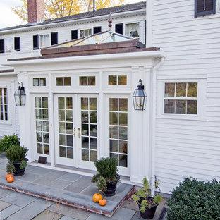 Inspiration pour une petit véranda victorienne avec un sol en calcaire, un poêle à bois, un manteau de cheminée en pierre et un plafond en verre.