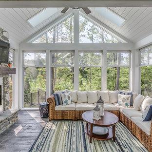 Esempio di una veranda tradizionale con camino classico, cornice del camino in metallo, lucernario, pavimento grigio e pavimento in legno verniciato