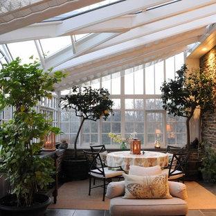 Cette image montre une grand véranda traditionnelle avec un plafond en verre et un sol en ardoise.