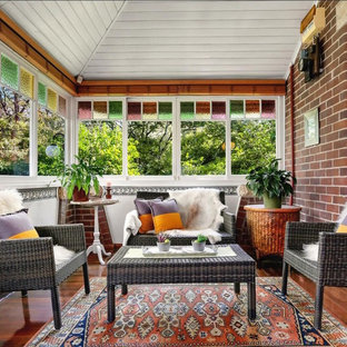 This is an example of a mid-sized traditional sunroom in Sydney with medium hardwood floors, a standard ceiling and brown floor.