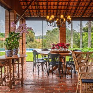 Inspiration pour une véranda rustique avec un sol en brique, un plafond standard et un sol rouge.