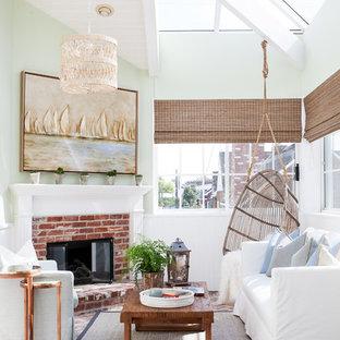 Imagen de galería marinera con chimenea tradicional, marco de chimenea de ladrillo y techo de vidrio