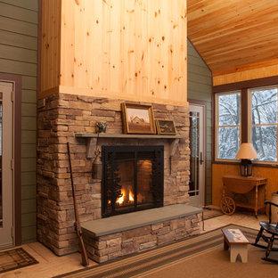Exempel på ett mellanstort amerikanskt uterum, med plywoodgolv, en dubbelsidig öppen spis, tak och en spiselkrans i sten