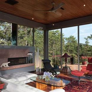 Cette photo montre une grand véranda sud-ouest américain avec un sol en bois foncé, une cheminée standard, un manteau de cheminée en pierre et un plafond standard.