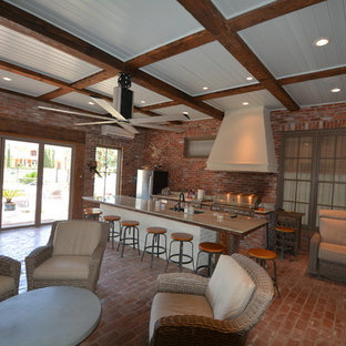 Photo of a large urban conservatory in New Orleans with brick flooring and a standard ceiling.