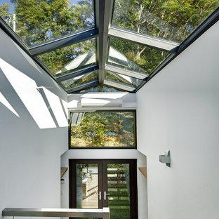 Inspiration för stora moderna uterum, med ljust trägolv, en standard öppen spis och glastak