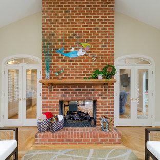 Idée de décoration pour une véranda tradition de taille moyenne avec un sol en bois brun, une cheminée double-face et un manteau de cheminée en brique.