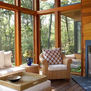 Inspiration pour une véranda design de taille moyenne avec une cheminée d'angle, un manteau de cheminée en pierre, un plafond standard et un sol en bois foncé.
