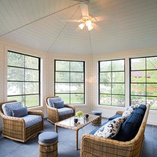 Cette photo montre une grand véranda chic avec un plafond standard, un sol gris, un sol en ardoise et aucune cheminée.