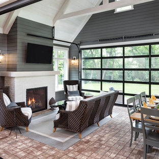 This is an example of a medium sized classic conservatory in Minneapolis with brick flooring, a standard fireplace, a brick fireplace surround, a standard ceiling and red floors.