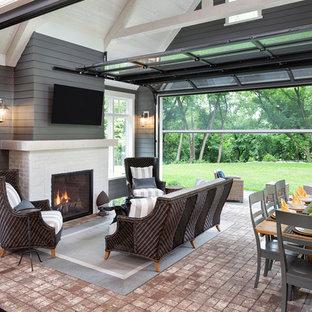 Réalisation d'une véranda tradition de taille moyenne avec un sol en brique, une cheminée standard, un manteau de cheminée en brique, un plafond standard et un sol rouge.
