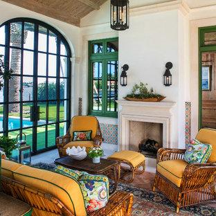 Inspiration pour une grand véranda méditerranéenne avec béton au sol, une cheminée standard, un manteau de cheminée en pierre, un plafond standard et un sol beige.