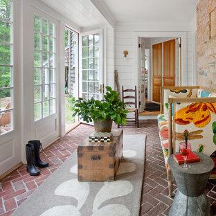 Ejemplo de galería campestre con suelo de ladrillo, techo estándar y suelo rojo