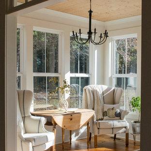 Immagine di una veranda country di medie dimensioni con pavimento in legno massello medio, soffitto classico e pavimento marrone