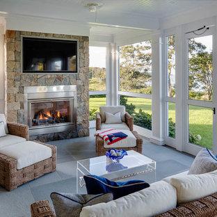 Aménagement d'une véranda bord de mer de taille moyenne avec béton au sol, une cheminée standard, un manteau de cheminée en pierre et un plafond standard.
