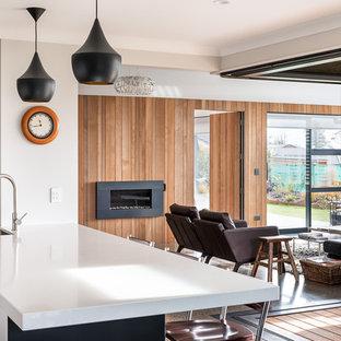 Idées déco pour une grand véranda contemporaine avec béton au sol, cheminée suspendue, un manteau de cheminée en métal et un sol multicolore.
