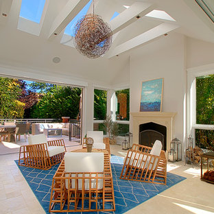Large island style travertine floor and beige floor sunroom photo in Chicago with a standard fireplace, a stone fireplace and a skylight
