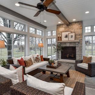 Cette photo montre une véranda nature avec un sol en ardoise, une cheminée standard, un manteau de cheminée en pierre et un plafond standard.
