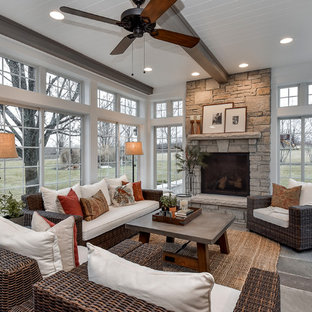 Inspiration for a cottage slate floor sunroom remodel in Chicago with a standard fireplace, a stone fireplace and a standard ceiling