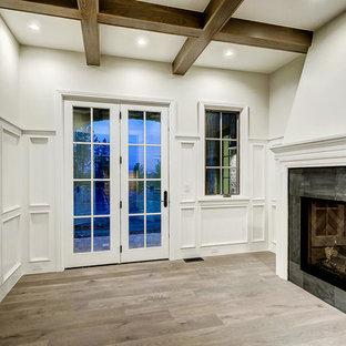Inspiration pour une véranda traditionnelle de taille moyenne avec un sol en bois clair, une cheminée double-face, un manteau de cheminée en carrelage, un plafond standard et un sol marron.