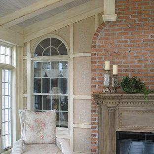 Exempel på ett mellanstort klassiskt uterum, med betonggolv, en standard öppen spis och en spiselkrans i trä