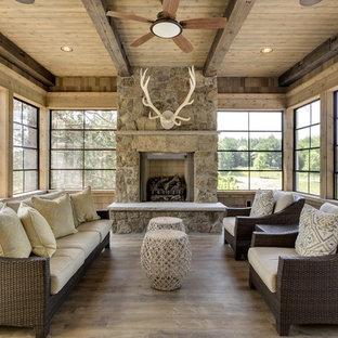Diseño de galería rural, de tamaño medio, con suelo de madera en tonos medios, chimenea tradicional, techo estándar, suelo gris y marco de chimenea de piedra