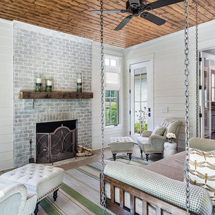 Large farmhouse conservatory in Other with a wood burning stove, a brick fireplace surround, a standard ceiling, concrete flooring and grey floors.
