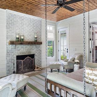 Modelo de galería de estilo de casa de campo, grande, con estufa de leña, marco de chimenea de ladrillo, techo estándar, suelo de cemento y suelo gris