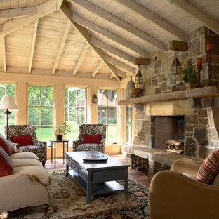 Klassisk inredning av ett uterum, med en spiselkrans i tegelsten, tak, klinkergolv i terrakotta och rött golv