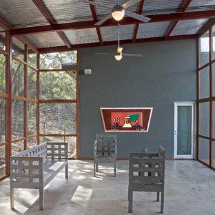 Cette photo montre une très grand véranda moderne avec un plafond standard, béton au sol, aucune cheminée et un sol gris.