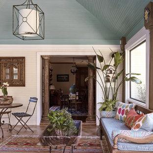 Cette photo montre une véranda exotique de taille moyenne avec aucune cheminée, un plafond standard et un sol en carreau de terre cuite.