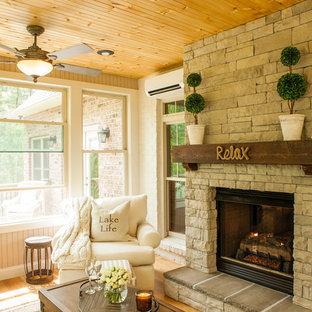 Aménagement d'une véranda campagne avec un sol en bois clair, un manteau de cheminée en pierre, un plafond standard et une cheminée standard.