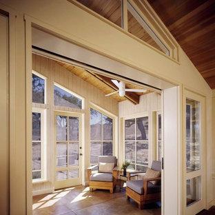 Immagine di una veranda country con soffitto classico, pavimento in cemento e pavimento marrone